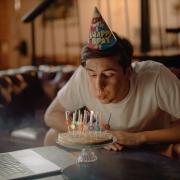 Jongen blaast kaarsjes op taart uit en draagt een feesthoedje