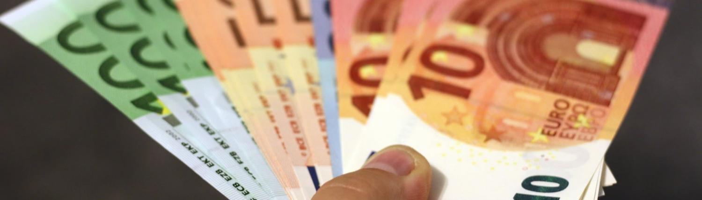 Iemand houdt eurobiljetten vast in een waaier - sparen