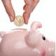 iemand stopt een munt in een roze spaarvarken