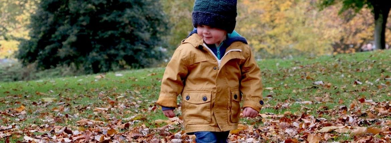 Jongetje loopt door de herfstbladeren-herfstactiviteiten